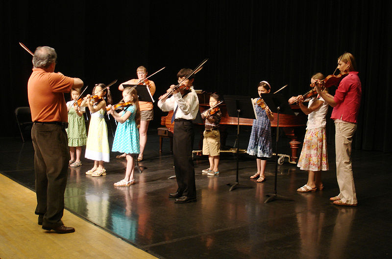 Teacher and young students playing a Suzuki violin recital