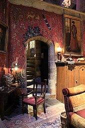 Une salle chaleureuse aux teintes rouges, avec tapisseries médiévales, tapis, fauteuil, meubles en bois et escalier de pierre en colimaçon menant à l'étage.