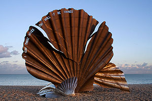 "Maggi Hambling - Hambling's Scallop (2003) stands on the north end of Aldeburgh beach. It is a tribute to Benjamin Britten and is pierced with the words ""I hear those voices that will not be drowned"" from his opera Peter Grimes."