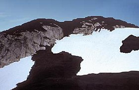 Rugged mountain covered with dark rock on its summit and flanks. Dark rock and patches of glacial ice loom in the foreground.