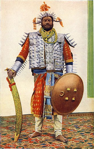 Executioner - Photograph (hand-coloured), original dated 1898, of The Lord High Executioner of the former princely state of Rewah, Central India, with large executioner's sword (Tegha sword)