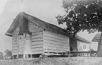 Dogtrot house - One of several dogtrot houses formerly used as slave quarters at the plantation of Thornhill near Forkland, Alabama.  This photograph was taken in 1934, the dwelling was subsequently destroyed.  Note the split-shingle roof and stick-and-mud chimney.