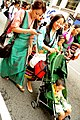 Tibetan women texting and pushing stroller.jpg