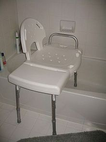 A white plastic bench sits with two legs inside a bathtub and two legs outside the tub resting on the floor.