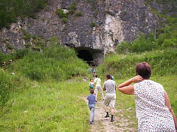 Tourists at the entrance to Denisova Cave, Rus...