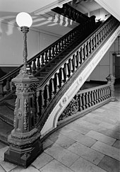 Ornate cast iron staircase with a lamppost atop the newell