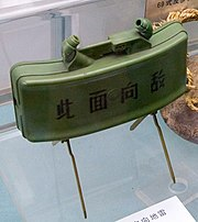 """A green plastic-bodied mine supported by a pair of scissor legs, with the text """"此面向敌"""" (this side towards enemy) on the front."""