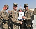 U.S. Army Brig. Gen. Duane Gamble, center, the deputy commanding general of the 1st Sustainment Command, awards a Combat Action Badge to Spc. Thomas J. Johnson, with the 864th Engineer Battalion, assigned to 131007-A-WQ129-010.jpg