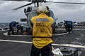 U.S. Navy Boatswain's Mate 2nd Class Joshua Husic signals to the pilots of an MH-60S Seahawk helicopter assigned to Helicopter Sea Combat Squadron (HSC) 9 as Sailors attach chocks and chains during flight 131214-N-AP176-122.jpg