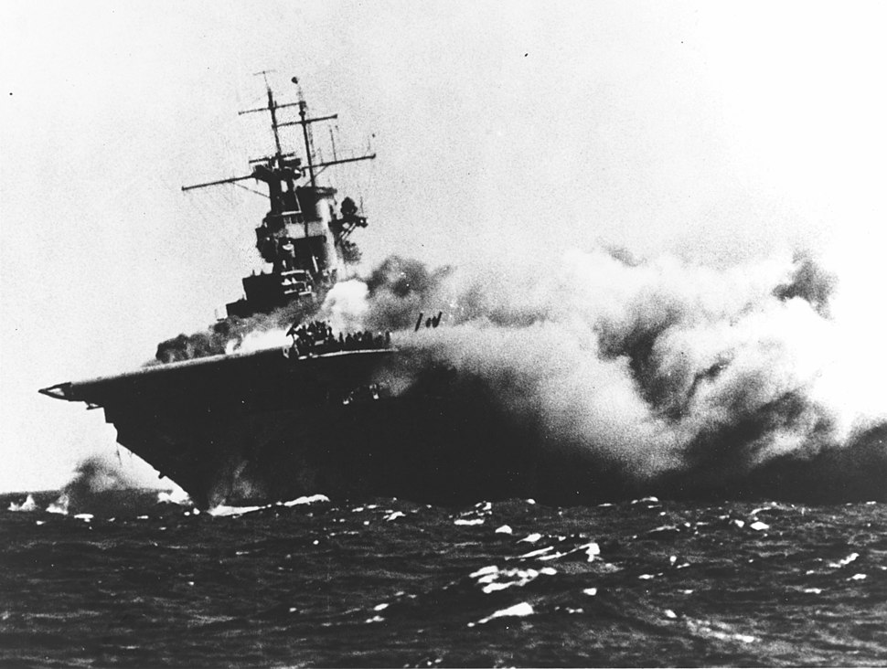 Ship listing to one side, with smoke billowing out