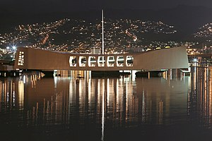 Alfred Preis - USS Arizona Memorial is bathed by the lights of 'Aiea on the evening of the 62nd anniversary of the attack on Pearl Harbor, December 7, 2003.