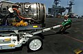 US Navy 040908-N-6213R-002 Aviation Machinist's Mate 3rd Class Joshua Ray of Amherst, Va., positions an engine skid supporting an F110-GE-400 turbofan jet engine across the flight deck aboard USS John C. Stennis (CVN 74).jpg