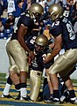 US Navy 041023-N-9693M-011 U.S. Naval Academy Midshipman 1st Class Eric Roberts, left, and Midshipman 2nd Class Mick Yokitis, right, congratulate Midshipman 1st Class Corey Dryden on a recovered fumble in the end zone.jpg