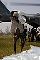 US Navy 071127-N-5642P-189 A local resident carries a bag of fresh water off of the CH-53E Sea Stallion helicopter that is there delivering relief supplies.jpg