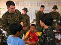US Navy 080220-N-0807W-199 Lt. Todd E. Gregory, attached to 31st Marine Expeditionary Unit, speaks to a translator from the armed forces of the Philippines to help facilitate proper medical attention during a medical and dental.jpg