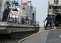 US Navy 080627-N-7668G-057 Electrician's Mate 2nd Class Michael P. Ojea Sr. throws a line to Hull Technician 2nd Class Lemar Carter to moor a Scheduled Preservation Upkeep Coordinated Effort (SPRUCE) Barge.jpg