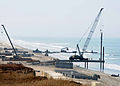 US Navy 080711-N-1424C-965 The Joint Logistics Over-The-Shore 2008 beachhead is expanded by an elevated causeway as support piles are driven into the beach while a Navy lighterage is off loaded in the distance.jpg