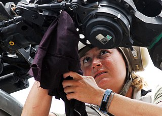 Helicopter pilot cleaning a rotor blade of her helicopter
