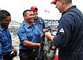 US Navy 111003-N-ED900-191 Damage Controlman 1st Class Chad Simon gives a self-contained breathing apparatus to a Royal Brunei Navy member.jpg