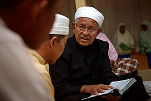 Religion in Malaysia - An Ustaz reading during a Malay wedding