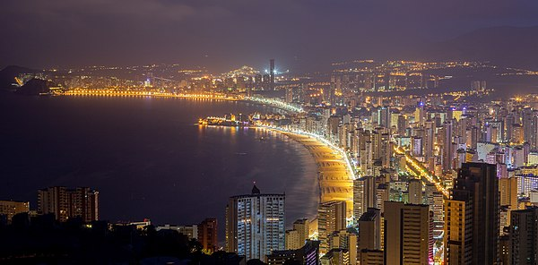 High dynamic range night shot of Benidorm, turistic capital of the Costa Blanca (literally White Coast) in Land of Valencia, Spain. The shot was taken from the Cross of Benidorm, located on the summit of the Sierra Helada. Benidorm, is a town with 73,000 inhabitants throughout the year but with a peak of over half a million in the summer season. It's the third town with the most concentration of tall buildings in Europe, after London and Milan, whereas in Spain, Benidorm is positioned third, behind Barcelona and Madrid in the total number of skyscrapers. Nevertheless, Benidorm has the most high-rise buildings per capita in the world.