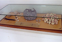 a glass display case containing stones and a pot