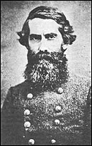 Old photo shows a frowning man wearing a double-breasted gray military uniform. He sports a beard so large that it hides the entire lower part of his face.