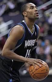 Wayne Ellington with a goatee and a Shape-Up hair style, wearing a black Timberwolves uniform with blue and white trim with a basketball