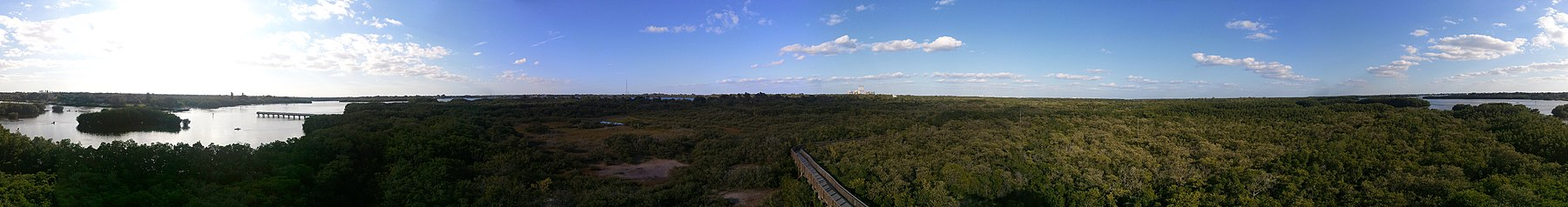 Panorama of mostly scrubby swamp, with various buildings/structures visible on the horizon.