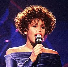 Whitney Houston performing, dressed in a strapless long-sleeve purple dress