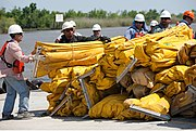 Men in hard hats standing near water next to large pile of bundled large yellow deflated rubber tubing