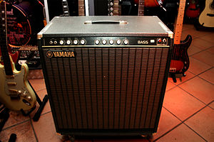 "Bass amplifier - A Yamaha B100-115 combo amp, which contains a 100 watt amplifier and one 15"" speaker in a wooden cabinet."