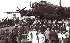 Crowd of uniformed and civilian personnel in front of four-engined military monoplane