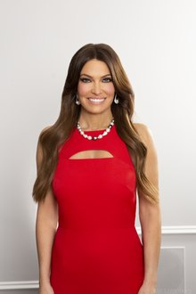 Guilfoyle posing and smiling in a red dress
