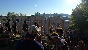 Osheaga Festival - Crowd gathers behind Osheaga sign. The skyline of Montreal can be seen from the Île Sainte-Hélène, where the festival is held.