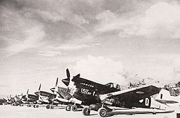 Row of single-engined fighter aircraft parked on airfield