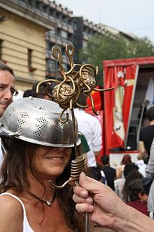 "smiling woman wearing a colander on her head being ""blessed"" by a brass Flying Spaghetti Monster in the style of a Roman Catholic scepter."