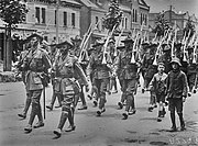 Soldiers marching along a city street