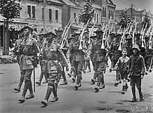 Soldaten marschieren entlang einer Stadtstra?e