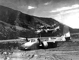 Three twin-engined military aircraft flying low over a valley
