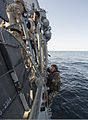 A French sailor assigned to the visit, board, search and seizure (VBSS) team with the French Navy destroyer Jean de Vienne (D 643) climbs a ladder tended by U.S. Navy Gunner's Mate 2nd Class Douglas 140101-N-PW661-035.jpg