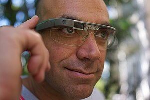 Optical head-mounted display - A man controls Google Glass using the touchpad built into the side of the device