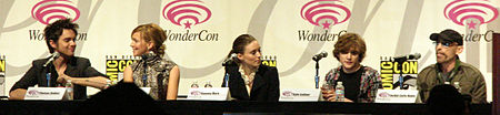Five actors from the cast, sitting at a long table, each with a microphone. The backdrop has the WonderCon logo. The actors from left to right are Dekker, Cassidy, Mara, Gallner, and Haley.