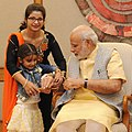 A child tying 'Rakhi' on the Prime Minister, Shri Narendra Modi's wrist, on the occasion of 'Raksha Bandhan', in New Delhi on August 29, 2015.jpg
