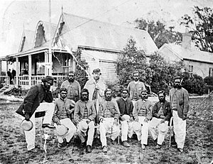 Melbourne Cricket Ground - Aboriginal cricket team with captain-coach Tom Wills, December 1866. In the background is the original MCC pavilion, built in 1854.