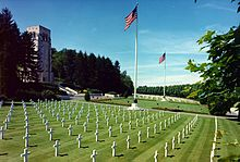 Photograph of field of graves marked with white crosses, with two American flags and a stone memorial building