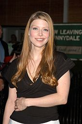 "Amber Benson stands, smiling, with her left forearm over her waist.  Behind her is a green banner that reads ""Now leaving Sunnydale. Come back soon."""