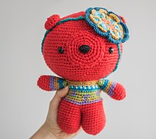 A red stuffed bear, wearing a blue and green sweater, with a flower decoration on the head