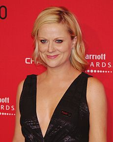 A shot of a blond woman wearing a black dress, smiling and looking at something outside the image.
