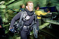 An Aussie diver in wetsuit from Australian Clearance Diving Team One carries his oxygen closed circuit rebreather (over right shoulder) to the stern deck ramp of USS Denver (LPD 9) for a night dive with the rest 970618-N-TU986-001.jpg